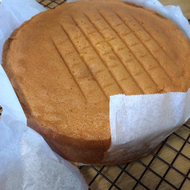 13. 整个模具从离操作台10厘米的f地方向下摔1-2此,震破大气泡。放入160C的烤箱33-35分钟。烤好的蛋糕油纸呈波浪状,高度左模具中有6厘米左右高。蛋糕取出连模具在离操作台15厘米处向下摔,避免脱模缩小。倒扣在晾架上脱模,5-6分钟后将蛋糕翻面至完全冷却。