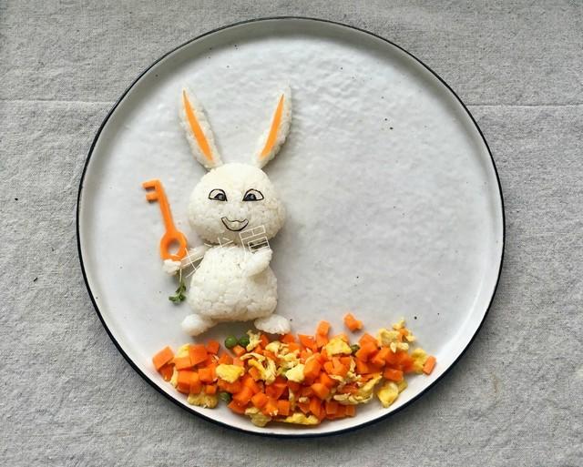 用胡萝卜切出钥匙的形状,放到兔子手中.把炒好的萝卜丁放到餐盘底部.