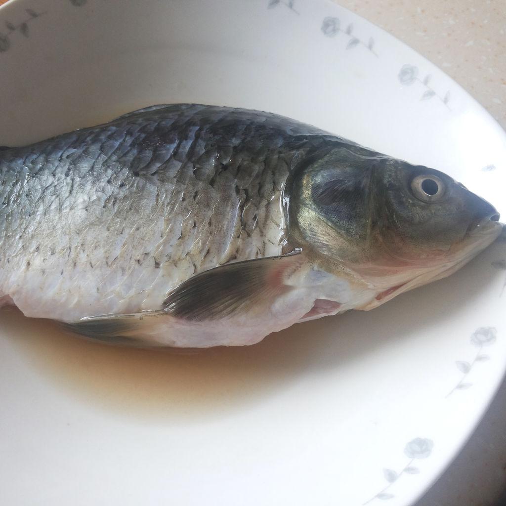 鲫鱼刮鳞,去鳃,破肚去内脏冲洗干净,用盐均匀涂抹鱼身,放黄酒腌制