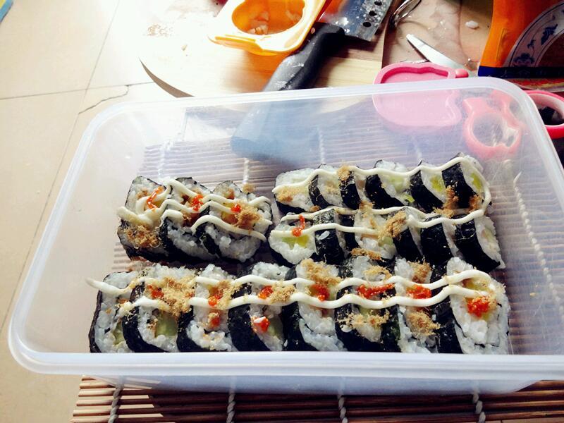 1. 把黄瓜 火腿 黄萝卜 肉松 沙拉 寿司醋 准备好 珍珠米(寿司米)米和水的比例为1:1煮熟 饭还很热时加入寿司醋 可以多加点 差不多之后等米饭冷了之后平铺在紫菜上 用饭勺压紧一点 别铺太厚了 然后把食材放在米饭上 切记 不要把食材放在正中间 一定要在下方 铺完后 依据个人口味可以加入些沙拉 肉松 然后开始卷